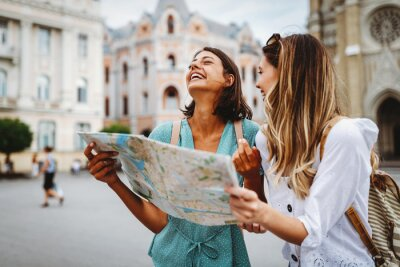 Naklejka Fun, friends, travel and tourism concept. Beautiful girls looking for direction in the city