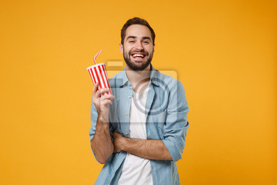 Naklejka Funny young man in casual blue shirt posing isolated on yellow orange wall background, studio portrait. People sincere emotions lifestyle concept. Mock up copy space. Hold in hand cup of soda or cola.