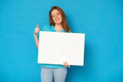 Naklejka Ginger girl holding a whiteboard on blue background.