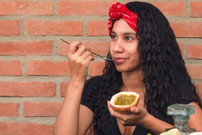 Naklejka Girl with a red scarf on her head enjoys the tropical flavor of a passion fruit