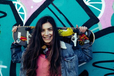 Naklejka Girl with skateboard graffiti wall background