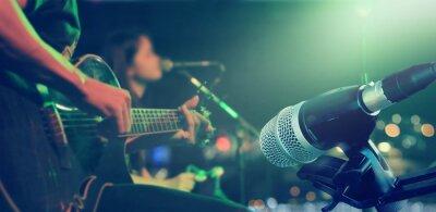 Naklejka Gitarzysta na scenie z mikrofonem na tle, miękki i rozmycia pojęcia