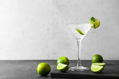 Naklejka Glass of tasty margarita cocktail and limes on light background