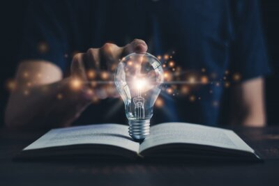 Naklejka Glowing light bulb and book or text book with futuristic icon. Self learning or education knowledge and business studying concept. Idea of learning online class or e-learning at home.