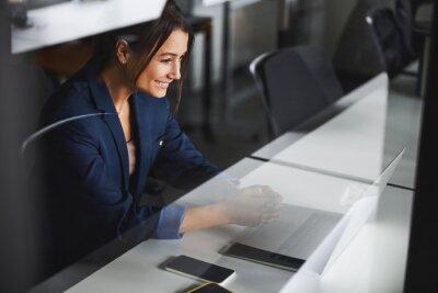 Naklejka Gorgeous business lady wearing dark blue jacket looking to the screen of laptop in room indoors