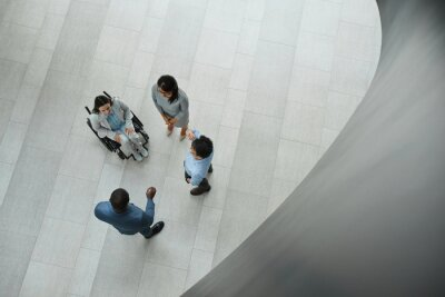 Naklejka Graphic top down view at young businesswoman in wheelchair talking to diverse group of people in office lobby, copy space