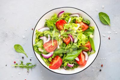 Naklejka Green salad from fresh leaves and tomatoes.