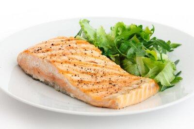 Naklejka Grillowany filet z łososia na talerzu z zieloną sałatą.