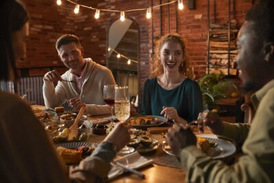 Naklejka Group of cheerful adult people sitting at dinner table while enjoying party with outdoor lighting