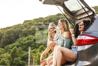 Naklejka Group of female best friends on travel . They sitting on car trunk and relaxing after long journey.