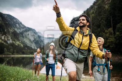 Naklejka Group of happy friends with backpacks hiking together