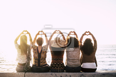 Naklejka Group of happy people  outdoor friends women viewed from back doing love hearth sign with up hands - concept of relationship - sunset and sea in background