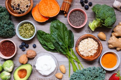 Naklejka Group of healthy food ingredients. Overhead view table scene on a wooden background. Super food concept with green vegetables, berries, whole grains, seeds, spices and nutritious items.