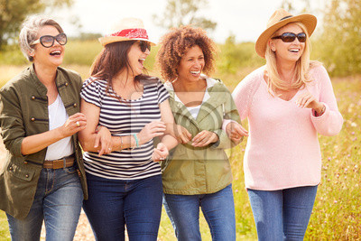 Naklejka Group Of Mature Female Friends Walking Along Path Through Yurt Campsite