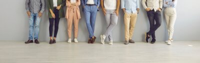 Naklejka Group of successful confident business people in smart and casual wear standing in studio. Team of employees leaning on grey office wall. Cropped shot of people's legs in classic pants and jeans
