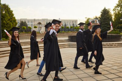 Naklejka Group of young smiling university graduates in traditional mantles walking, holding diplomas in raised hands feeling happy outdoors and celebrating graduation. Successful univesity graduation concept