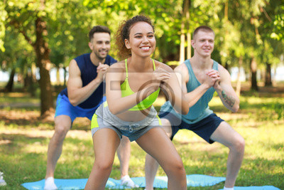 Naklejka Group of young sporty people training together outdoors