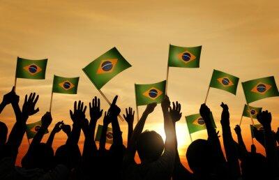Naklejka Grupa ludzi macha brazylijski Flagi w podświetleniem