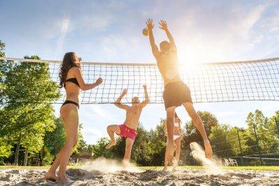 Naklejka Grupa młodych przyjaciół grając w siatkówkę na plaży