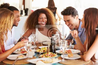 Naklejka Grupa młodych przyjaciół korzystających posiłek w restauracji na świeżym powietrzu