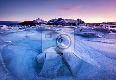 Grzbiet górski i odbicie na zamarzniętej powierzchni jeziora. Naturalny krajobraz na Lofotach, Norwegia. Woda i góry podczas zachodu słońca.