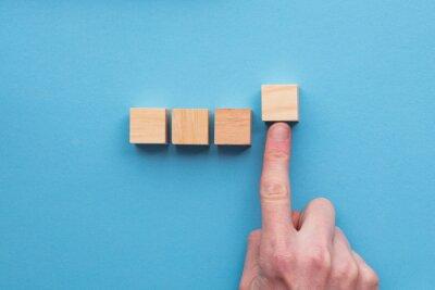Naklejka Hand choosing a wooden block from a set. Business choice concept