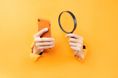 Naklejka Hand holding magnifying glass and phone protruding from background