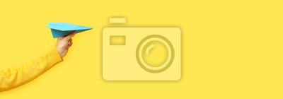 Naklejka hand holding paper plane over yellow background, panoramic mock up image