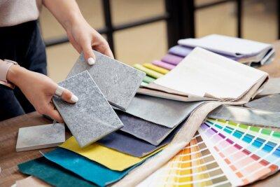 Naklejka Hand of woman designer chooses ceramic tile and set fabrics for curtains in textile. Concept design interior