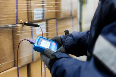 Naklejka Hand of worker using thermometer to temperature measurement in the goods boxes with ready meals after import in the cold room or warehouse for keep temperature room