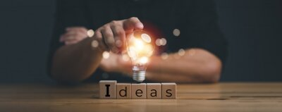 Naklejka hand touching on light bulb on wood block with Word Ideas, new idea concept with innovation and inspiration, innovative technology in science and communication concept.