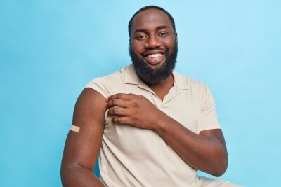 Naklejka Handsome bearded adult man with dark skin shows arm after vaccination being in good mood feels protected isolated over blue background. Immunization against coronavirus. Health care concept.