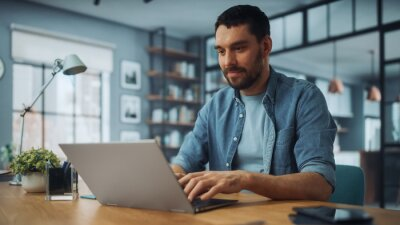 Naklejka Handsome Caucasian Man Working on Laptop Computer while Sitting on a Sofa Couch in Stylish Cozy Living Room. Freelancer Working From Home. Browsing Internet, Using Social Networks, Having Fun.