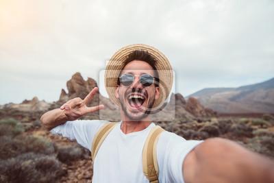 Naklejka Handsome hiker taking a selfie hiking a mountain using his smartphone