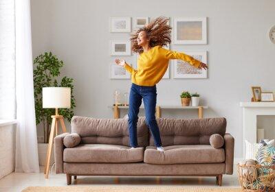 Naklejka Happy african american teen girl jumping on sofa while having fun on weekend at home