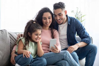 Naklejka Happy arabic family of three using smartphone at home, relaxing on couch