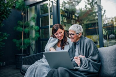 Naklejka Happy beautiful older mother and adult daughter using laptop while sitting on wooden terrace, portrait.