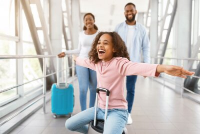 Naklejka Happy black family traveling with daughter, having fun in airport