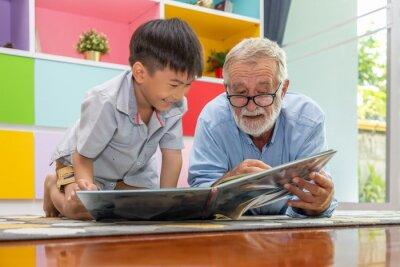 Naklejka Happy boy grandson reading book with old senior man grandfather at home