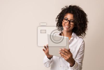 Naklejka Happy businesswoman using tablet over light background