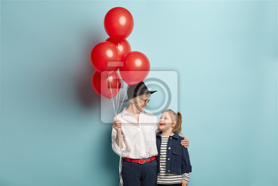 Naklejka Happy caring grandmother holds bunch of red air balloons, congratulates granddaughter with birthday, organize holiday, wear festive clothes, isolated over blue background. Grandmom embraces kid