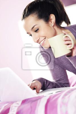 Happy casual młoda dama za pomocą laptopa, leżąc w łóżku