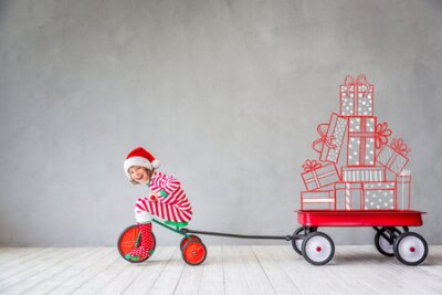 Naklejka Happy child in Christmas time. Funny kid playing at home. Xmas winter holiday concept