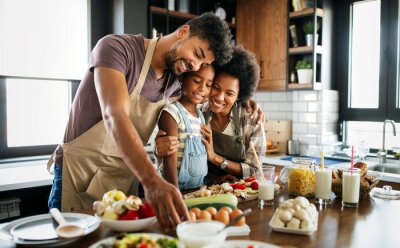 Naklejka Happy family preparing healthy food in kitchen together