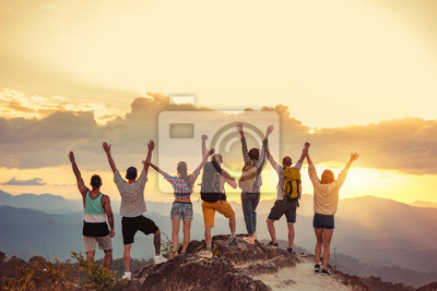 Naklejka Happy friends stands with raised arms against sunet mountains