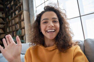 Naklejka Happy hispanic latin gen z teen girl blogger smiling face waving hand talking to webcam recording vlog, social media influencer streaming, making video call at home. Headshot portrait. Webcamera view