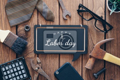Naklejka Happy Labor day background concept. Flat lay of construction blue collar handy tools and white collar's accessories over wooden background with text Happy Labor day on black chalkboard.