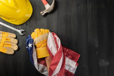 Naklejka Happy Labor day. Several engineer constructor work tools and , glove holding gripping US American flag with copy space on black dark background, Made in USA, American workforce concept