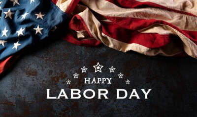 Naklejka Happy labor day text with America flag over black stone texture background.