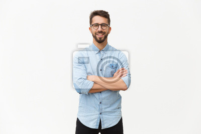 Naklejka Happy laughing guy posing with arms folded. Handsome young man in casual shirt and glasses standing isolated over white background. Male portrait concept